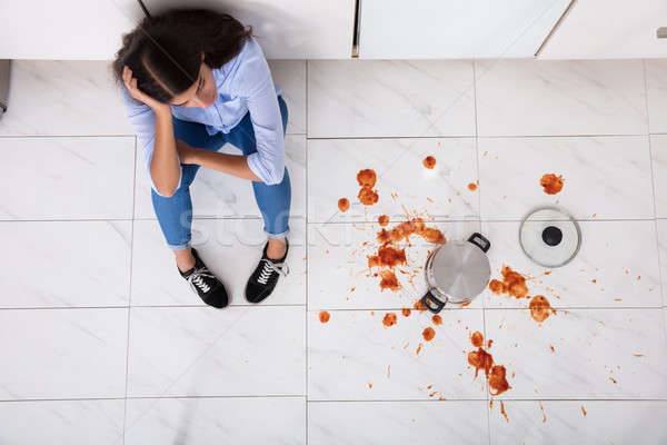 Woman Sitting On Kitchen Floor With Spilled Food Stock photo © AndreyPopov