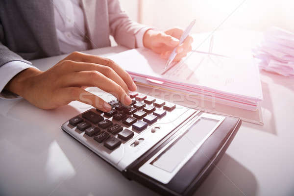 Businessperson Calculating Bills In Office Stock photo © AndreyPopov