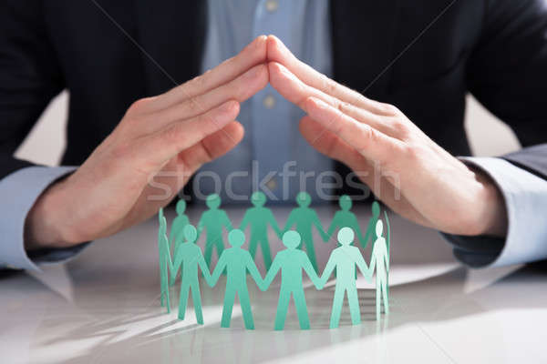 Businessperson's Hand Protecting Paper Cut Out Figures Stock photo © AndreyPopov