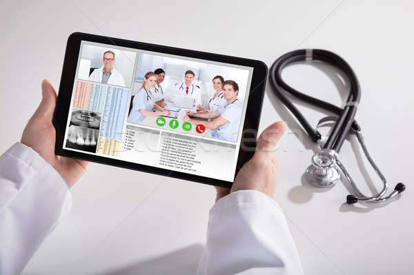 Doctor Video Conferencing With Medical Team On Digital Tablet Stock photo © AndreyPopov