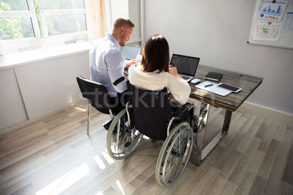 Disabled Businesswoman Sitting With Her Partner In Office Stock photo © AndreyPopov