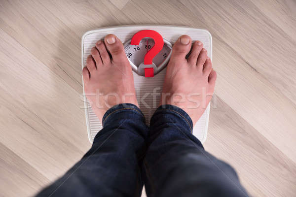 Person's Feet Standing On Weight Scale With Question Mark Sign Stock photo © AndreyPopov