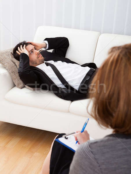 Business man talking to his psychiatrist explaining something Stock photo © AndreyPopov