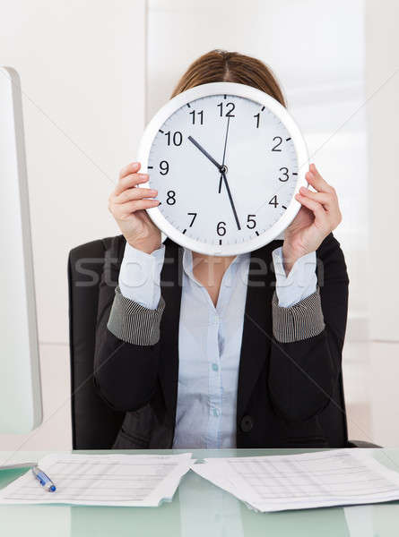 Businesswoman Holding Clock In Front Of Her Face In Office Stock photo © AndreyPopov