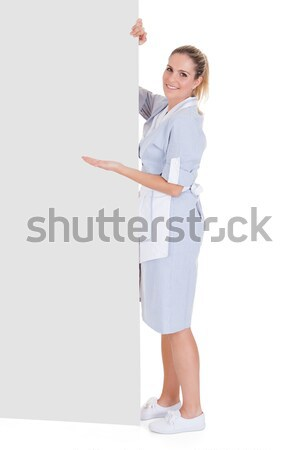 Young Maid Gesturing On Blank Placard Stock photo © AndreyPopov