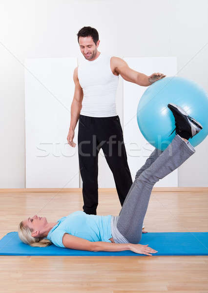 Instructor helping a woman with pilates exercises Stock photo © AndreyPopov