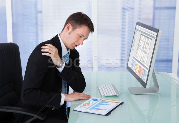 Businessman Having Shoulder Pain At Computer Desk Stock photo © AndreyPopov