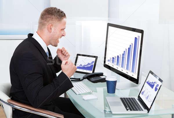 Businessman celebrating a performance graph Stock photo © AndreyPopov