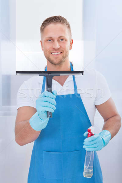 Male janitor using a squeegee to clean a window Stock photo © AndreyPopov