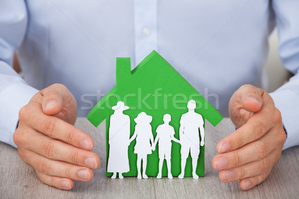Hands Protecting Green Model House And Family Stock photo © AndreyPopov