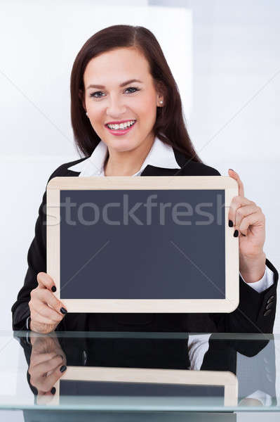 Businesswoman Holding Blank Chalkboard Stock photo © AndreyPopov
