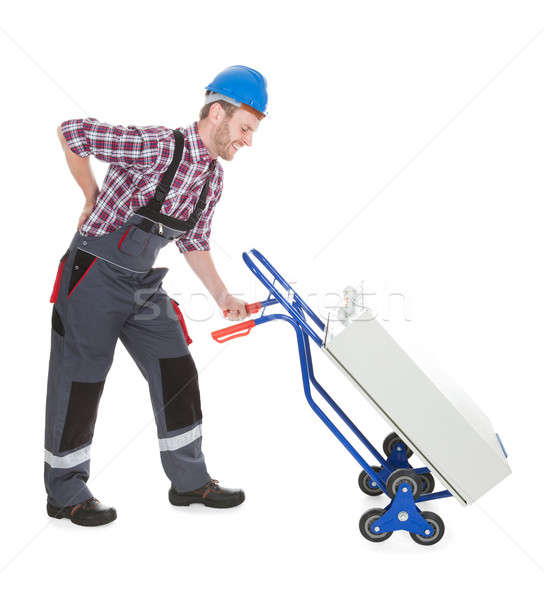 Worker Suffering From Backache While Pushing Machinery Stock photo © AndreyPopov