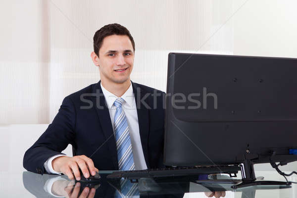 Young Businessman Using Computer At Office Desk Stock photo © AndreyPopov