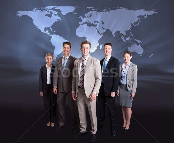 Confident Businesspeople Standing Against World Map Stock photo © AndreyPopov