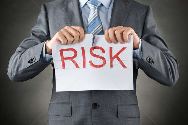 Businessman Tearing The Word Risk On Paper Stock photo © AndreyPopov