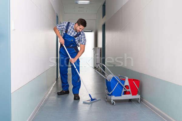 Homme travailleur balai nettoyage bureau couloir Photo stock © AndreyPopov