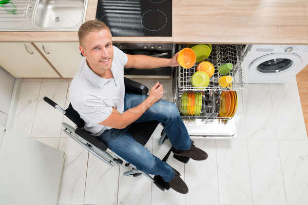 Disabled Man Arranging Plate In Dish Rack Stock photo © AndreyPopov