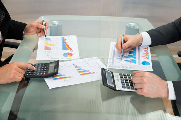Businessmen Analyzing The Graph On Office Desk Stock photo © AndreyPopov