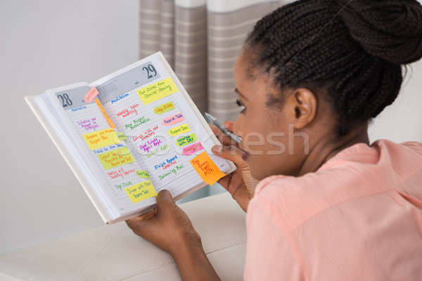 Young Woman Writing Schedule In Diary Stock photo © AndreyPopov