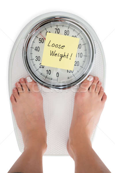 Woman Standing On Weight Scale With Loose Weight Note Stock photo © AndreyPopov