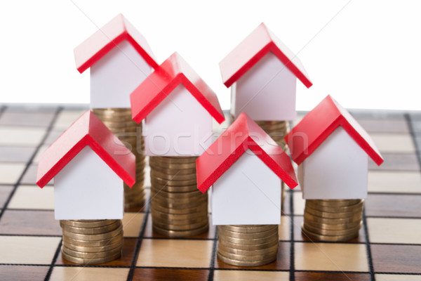 House Models And Stacked Coins On Chessboard Stock photo © AndreyPopov