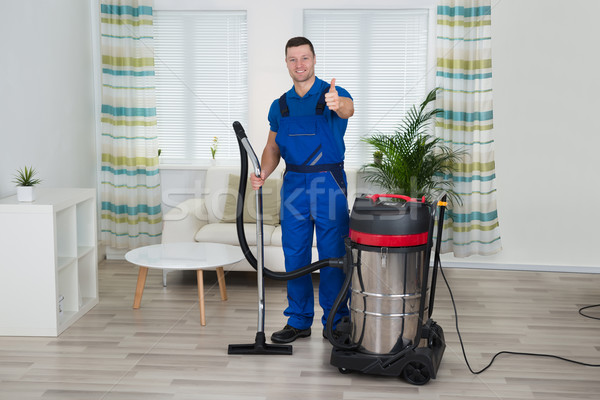 Janitor Showing Thumbs Up While Holding Vacuum Cleaner At Home Stock photo © AndreyPopov