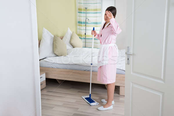 Exhausted Young Housekeeper With Mop Stock photo © AndreyPopov