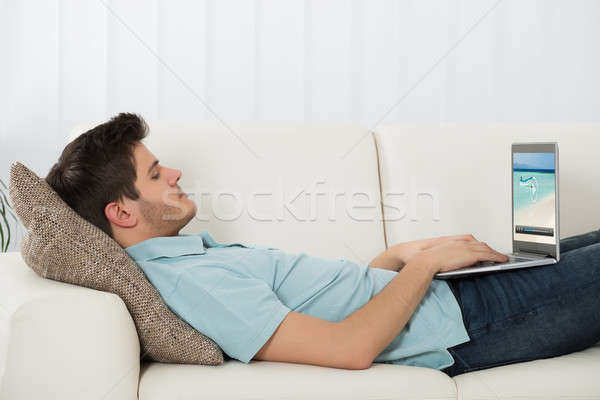 Man kijken video laptop jonge man sofa Stockfoto © AndreyPopov