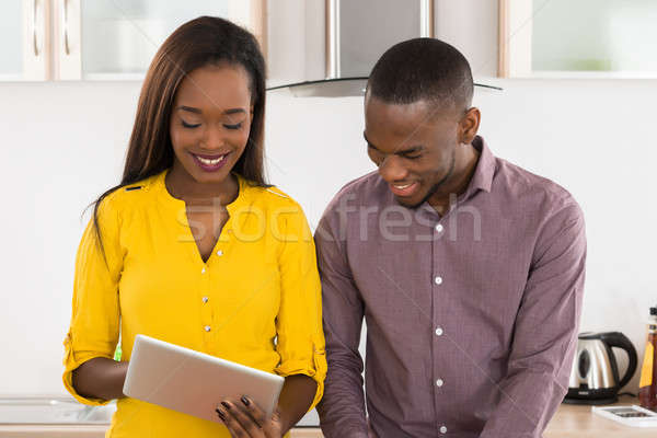 Man And Woman Using Digital Tablet In Kitchen For Recipe Stock photo © AndreyPopov