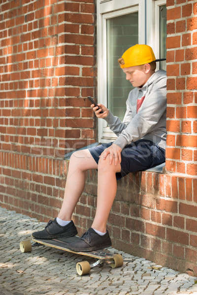 Boy With Skateboard Using At His Mobile Phone Stock photo © AndreyPopov