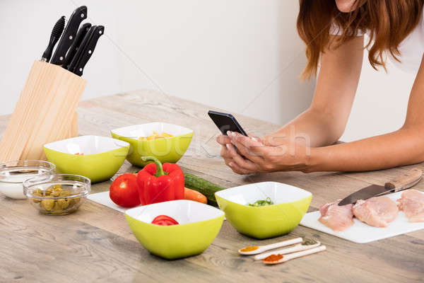 Woman Using Smartphone In Kitchen Stock photo © AndreyPopov