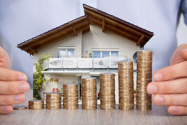 Man Securing House Model And Stack Of Coins Stock photo © AndreyPopov