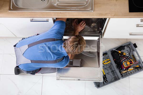 Férfi átfogó javít mosogatógép magasról fotózva kilátás Stock fotó © AndreyPopov