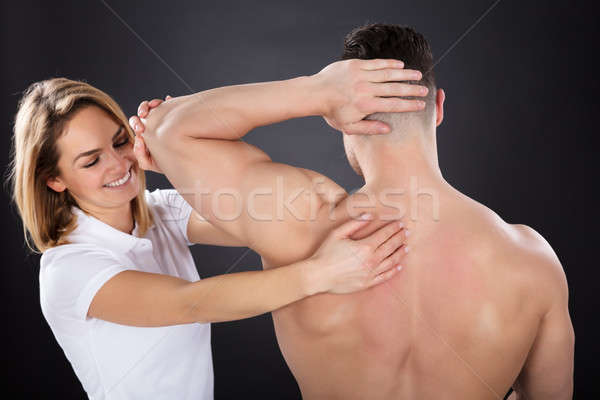 Smiling Female Physiotherapist Giving Shoulder Massage Stock photo © AndreyPopov