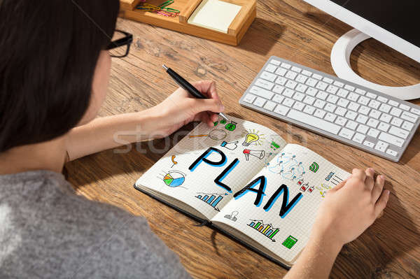 Businesswoman Drawing Plan Chart On Notebook Stock photo © AndreyPopov