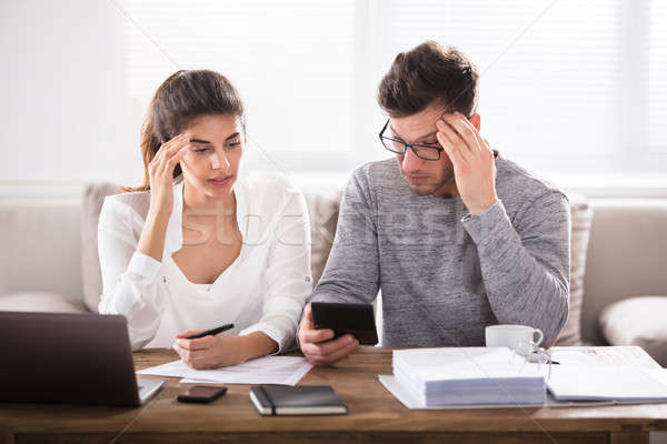 Worried Couple Looking At Calculator Stock photo © AndreyPopov