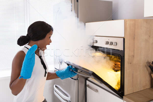 Shocked Woman Looking At Burnt Cookies In Oven Stock photo © AndreyPopov