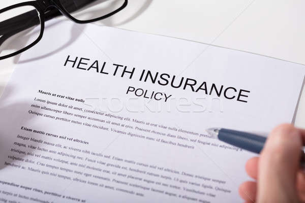 Person Holding Pen Over Health Insurance Policy Form Stock photo © AndreyPopov