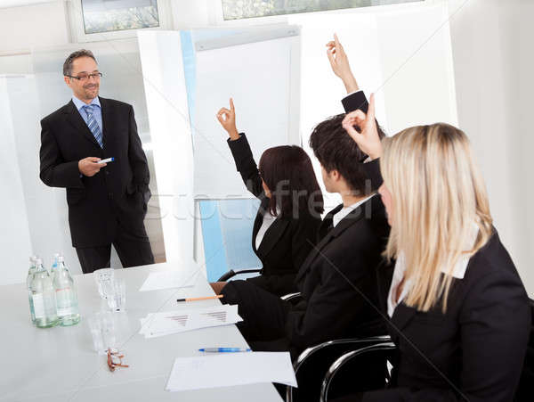 Business people at presentation raising hands Stock photo © AndreyPopov