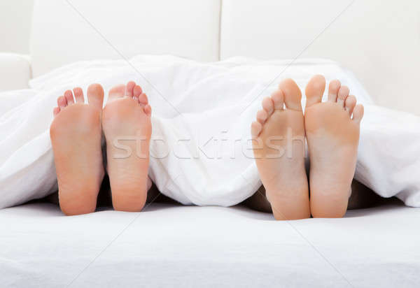 Close-up of couple's feet sleeping on bed Stock photo © AndreyPopov