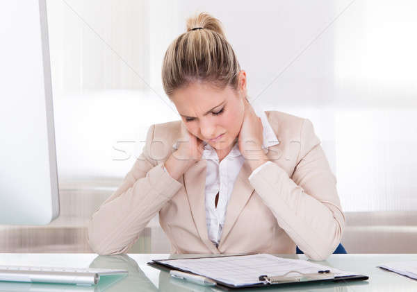 Young Businesswoman Suffering From Neck Pain At Office Stock photo © AndreyPopov