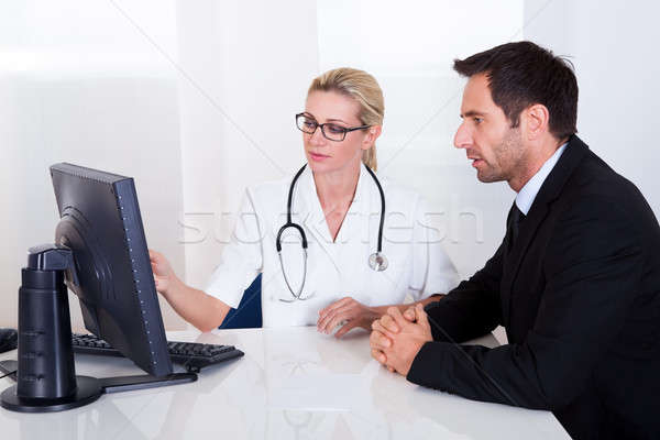 Orvos magyaráz valami férfi beteg vonzó nő Stock fotó © AndreyPopov