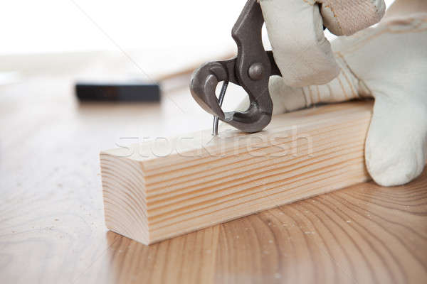 Worker pulling a nail from a plank Stock photo © AndreyPopov
