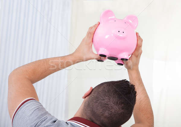 Rear view of young man checking out piggy bank Stock photo © AndreyPopov