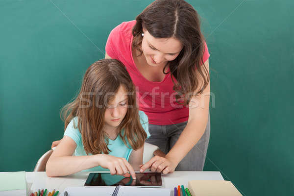 Teacher Assisting Girl In Using Digital Tablet Stock photo © AndreyPopov