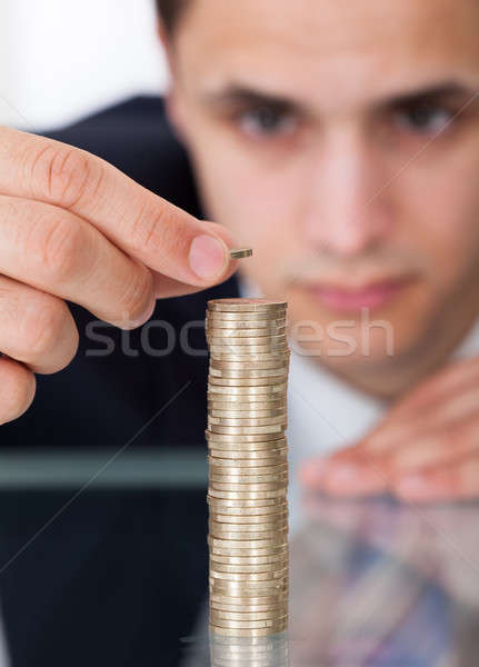 Businessman Stacking Coins At Desk Stock photo © AndreyPopov