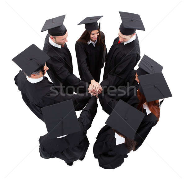 Stock photo: Graduate students stacking hands