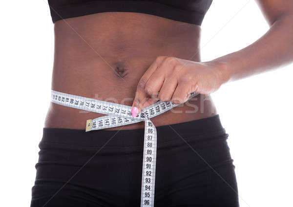 African American woman measuring waist with tape Stock photo © AndreyPopov