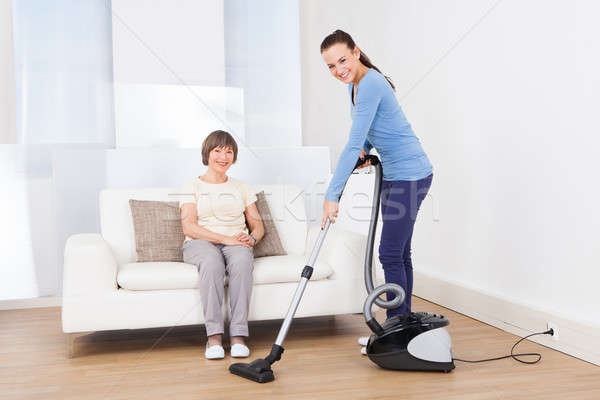 Caretaker Cleaning Floor While Senior Woman Sitting On Sofa Stock photo © AndreyPopov