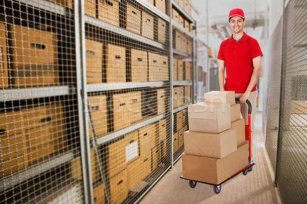 Delivery Man Pushing Cart Full Of Boxes In Warehouse Stock photo © AndreyPopov